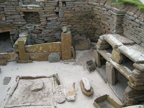 The cot at the back would have had straw or sheep skins for comfortable sleeping, the central pit was for heating cooking water using hot stones and there are storage shelves on the side of the home.
