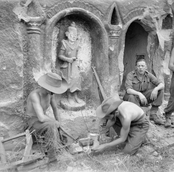 Men of the Wiltshire Regiment from the 26th Indian Infantry Division prepare a meal beside a temple on Ramree Island.
