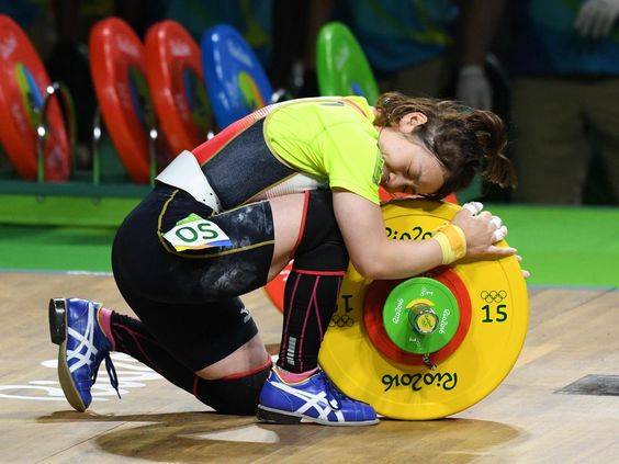 Hiromi Miyake (JPN) hugs the weights during the women's 48kg weightlifting event in the Rio 2016 Summer Olympic Games at Riocentro.  Robert Hanashiro-USA TODAY Sports
