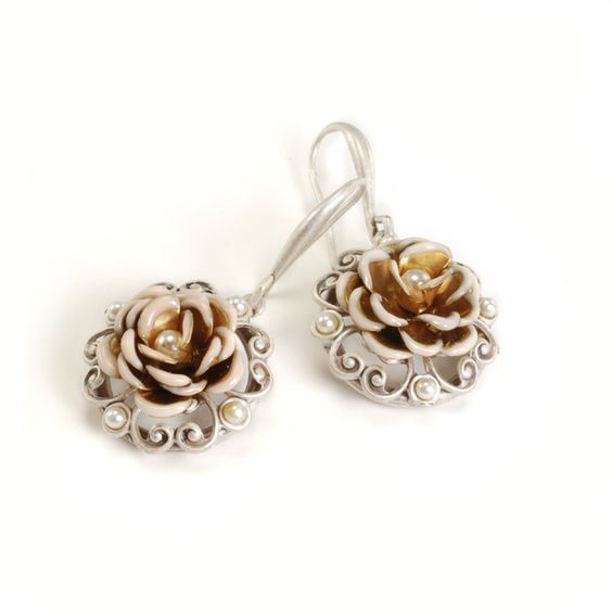 Detailed enamel roses adorn each of these earrings from Sweet Romance, complete with white faux pearls. Classic leverback clasps keep these silvertone pewter earrings in place.