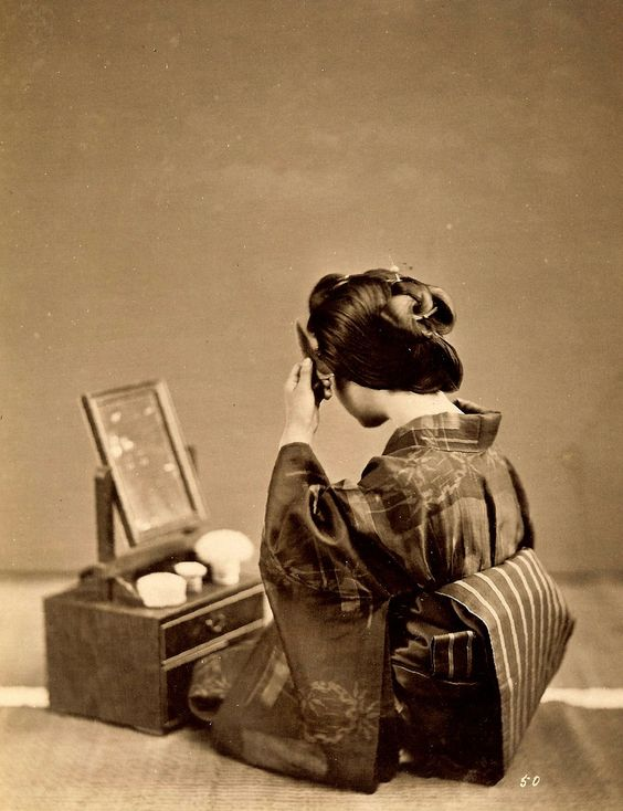 https://flic.kr/p/4yzVGi | GEISHA PREPARING TO GO OUT. | This simple 1870s photograph is nice for showing several aspects of the Geisha's hair, obi, and kimono.   日下部 金兵衛  (1841 - 1934):