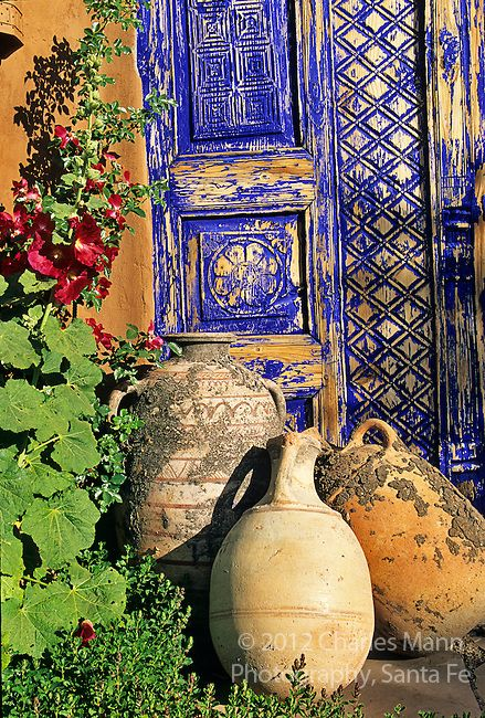 A big wooden gate is transformed into an exotic and mysterious entrance to a Santa Fe garden when painted with a coat of peeling cobalt blue paint.