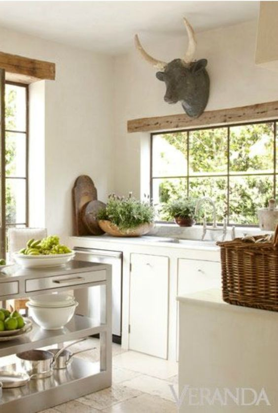 A European inspired white kitchen in Houston with design by Pamela Pierce. It appears that it could be a kitchen in the South of France with ox head, white cabinets, and stainless work island. #kitchen #frenchfarmhouse #european #frenchcountry #pamelapierce #rusticdecor #whitekitchen