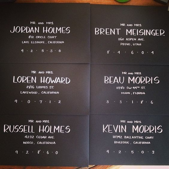 Block and Arch Deco scripts by KAKalligraphy. White ink on black envelopes.