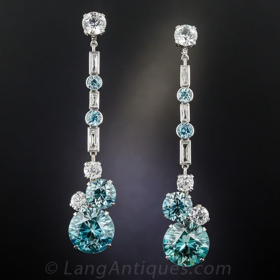 At just under 3 inches long (at full length, and 1 3/8 inches minus the removable center section), these handcrafted in 14K white gold, culminate with a matched pair of blue zircons (about 14 carats each, or 9/16 inch diameter). These in turn are crowned by a smaller pair of blue zircons (totaling 8.50 carats), along with two pairs of diamond white zircons. The extension sections alternate with white baguettes (zircons) and small blue zircons, surmounted by a white zircon stud. Circa 1930s-40s.