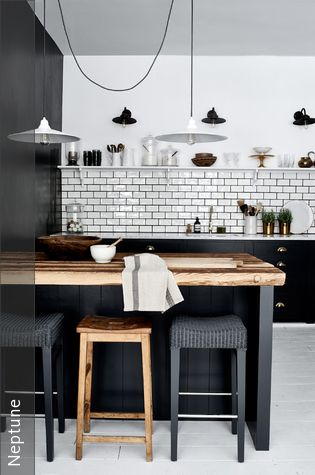 Eine Kücheneinrichtung in Schwarz und Weiß läuft unter Umständen Gefahr, zu steril zu wirken. Gut, wenn man ein Küchentresen aus Holz hat. Der setzt einen natürlichen Kontrast und erhöht die Wohnlichkeit der Küche.
