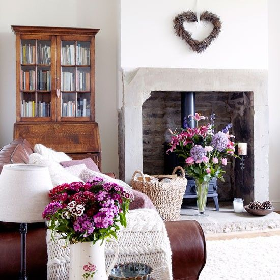 This decorating idea is the perfect balance of cool tones and warm textures; a stone fireplace and white walls are given a cosy makeover with wool rugs, buttery leather and aged wooden furniture.