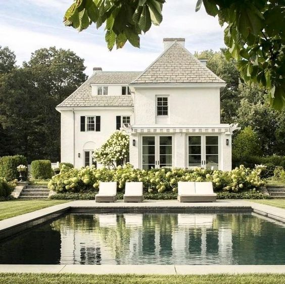 Beautiful white home. COME SEE these White House Exteriors With Traditional Architecture! #houseexterior #whitehouses #housedesign #whitepaintcolors #whitehomes #traditionalarchitecture #modernfarmhouses
