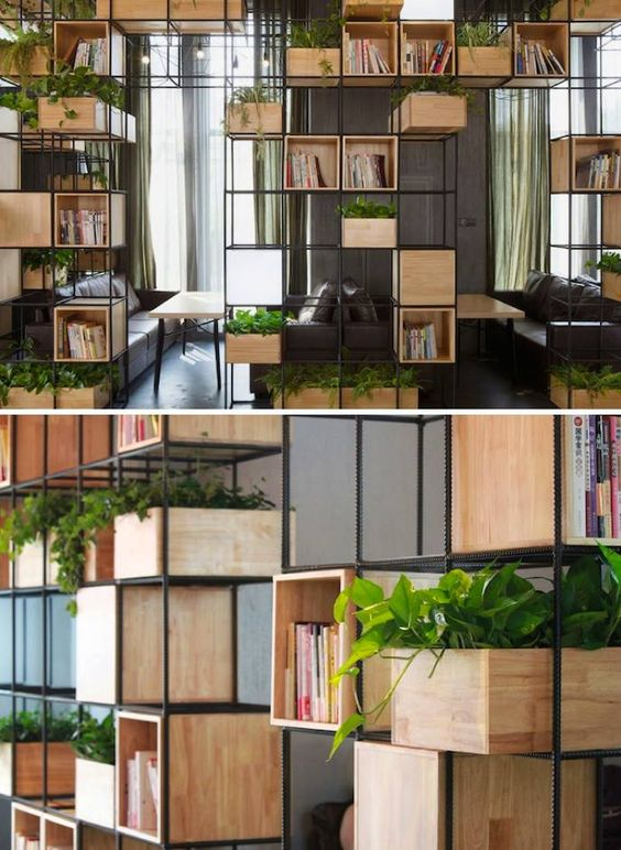 metal frame with wooden box room divider system to have distinction in space without a solid wall. Allows for greenery and storage.