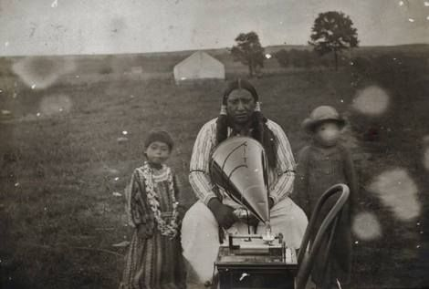 ?, Piiraski Riisaaru (aka Boy Chief, aka Henry Boy Chief), the husband of Bertha Boy Chief, recording a song onto a copper cylider as his unidentified daughter and son watches - Pawnee - 1905 on ArtStack #artist-3 #art