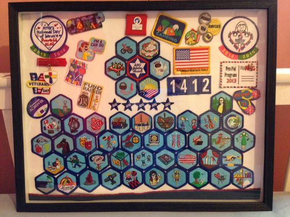 Tenderheart Badge Display. American Heritage Girls. AHG. Neckerchief along the bottom. Vest material behind AHG pin.