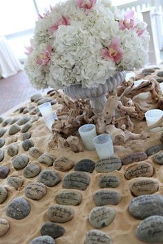Place card table centerpiece of hydrangea and pink cymbidium orchids accented with driftwood branches. Hand written guest place cards designed on river rocks placed on sand. Prefect for a beach wedding.