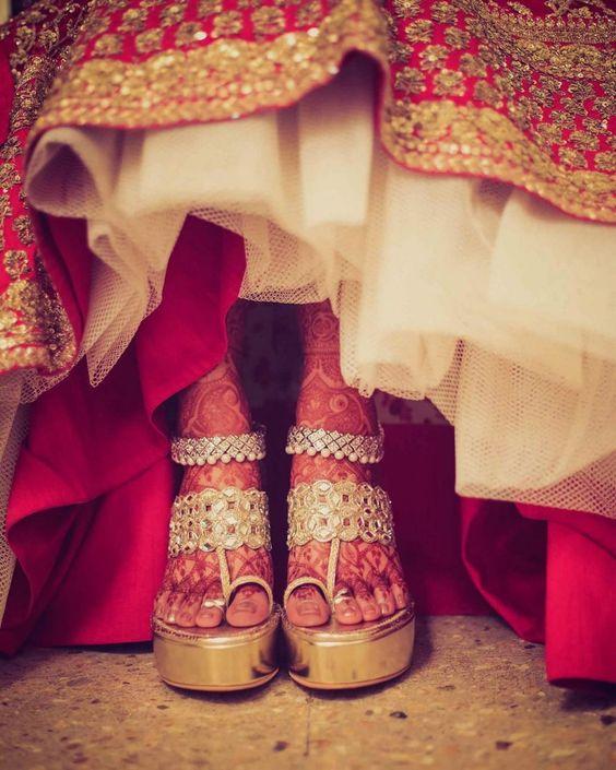 these golden wedges are super comfy and looks amazing with the red bridal lehenga #Trending, #TrendingBridalWear, #BridalWearInspirations, #Heels, #Wedges, #BridalFootwear #footwearinstyle #fashiontips #weddingheels
