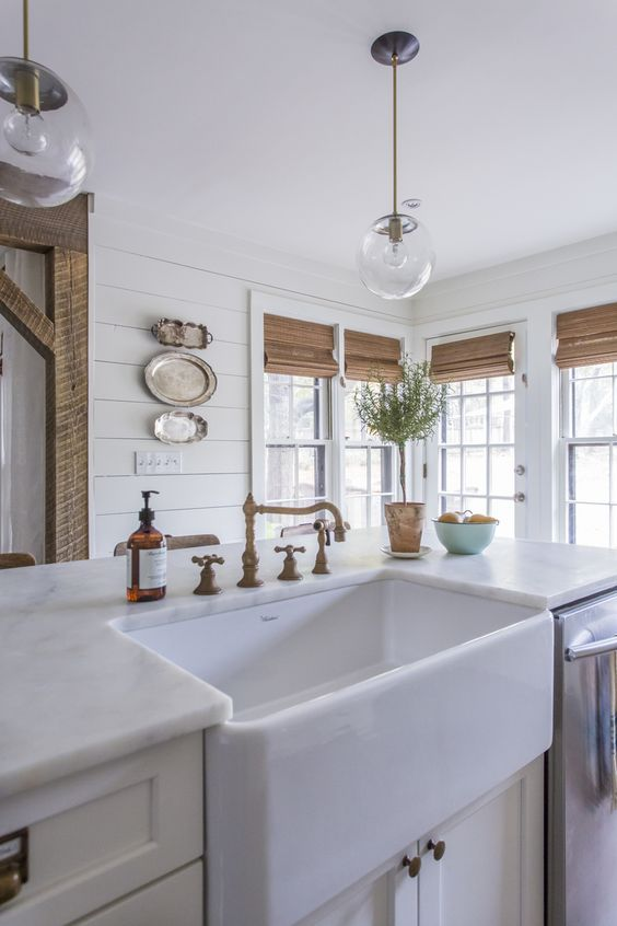 Love the unpolished brass faucet and farmhouse sink in this beautiful white kitchen eclecticallyvintage.com: