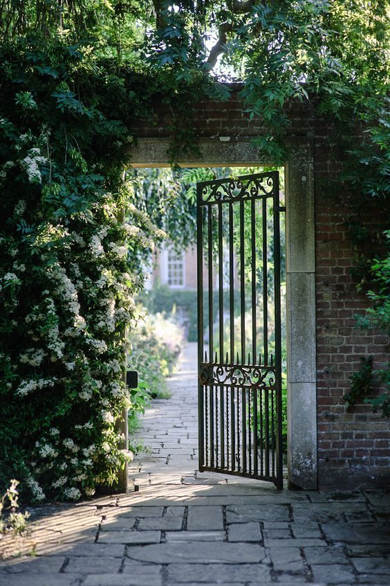 Garden gate ideas and inspiration: An iron garden gate framed by climbing vines leads to a beautiful path and courtyard. #gardengate #frenchcountry #provence #secretgarden #irongate