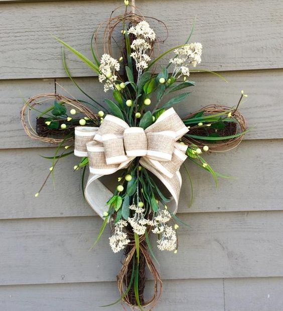 Grapevine Cross accented with faux greenery, berries, flowers and completed with a beautiful bow! The perfect addition to your home this Spring season...also makes a great gift! *cross measures 21x29