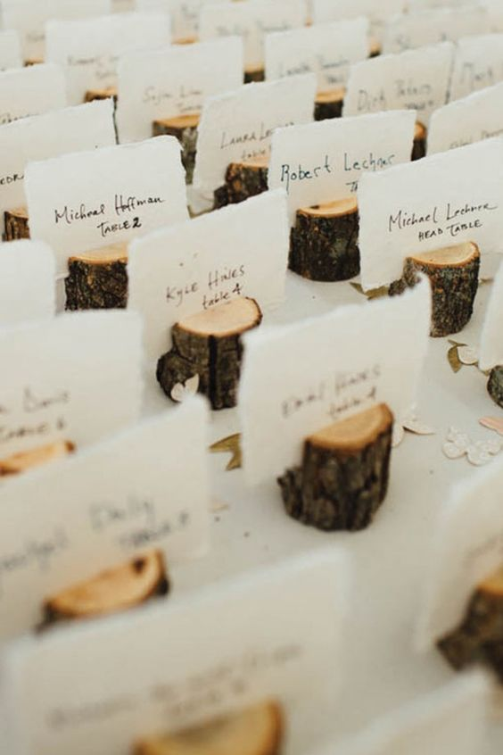 Handmade escort card holders pull the woodland look together, perfect for a winter wedding.