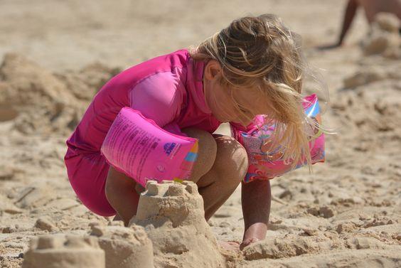 A girl building sandcastles on the beach