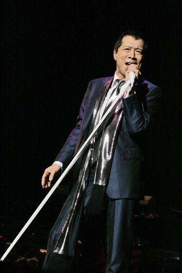 スーツ姿にサテンのスカーフをかけて歌っている矢沢永吉の画像