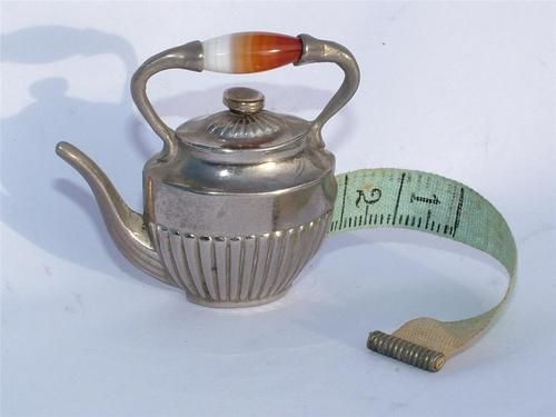 "RARE VICTORIAN MINIATURE 1.75"" SEWING TAPE MEASURE IN THE FORM OF A KETTLE AGATE 