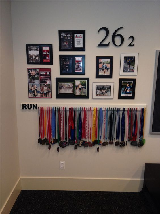 DIY medal display: paint a long simple baseboard and nail as many long nails as needed. Paint some loonie store letters and glue them on. Take your hard earned medals out of the box or drawer and hang them up. Keep at it!