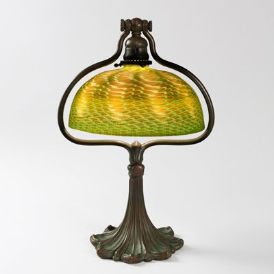"""This is not contemporary - image from a gallery of vintage and/or antique objects. Adjustable Desk - Glass and Bronze Tiffany Lamp  A Tiffany Studios New York Favrile glass and patinated bronze desk lamp. The green Damascene shade is ornamented with iridescent gold decoration and is suspended within a patinated bronze adjustable """"Harp"""" base with foliate design."""