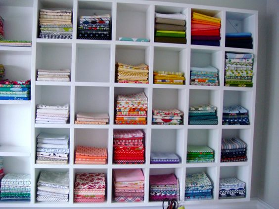 Such a beautiful sewing room, and inspiration right there! White sashing, colour-coordinated string blocks art quilt for the opposite wall! Ohh I do want my own lovely fabric storage like this....