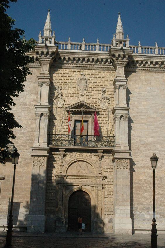 """Palacio de Santa Cruz (Antiguo Colegio de Santa Cruz), Valladolid. Fachada, detalle de la Portada.   Ésta se enmarca por dos contrafuertes que flanquean un paramento """"a lo romano"""". Contiene abundante decoración de grutescos, formada por arco de 1/2 punto más dos pilastras que soportan un entablamento sobre el que descansa un tímpano semicircular o """"frontón de vuelta redonda"""" con candeleros a ambos lados. En el timpano se representan al Gran Cardenal Mendoza y a Sta. Elena."""
