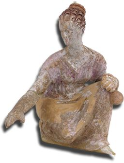 Figurine of a young woman playing knucklebones (astragaloi) 	  Material: Clay Provenance: Εretria, probably from a tomb. Date: End of 4th century BC