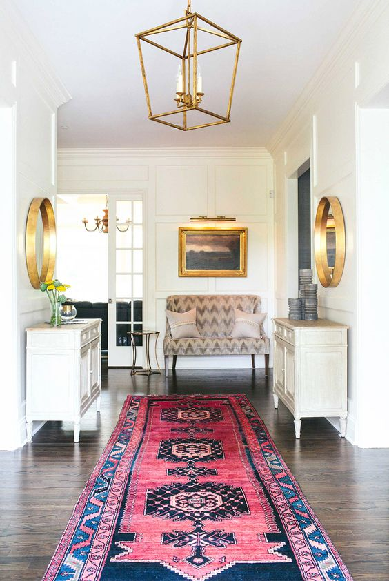 White and gold entryway with traditional Persian rug: