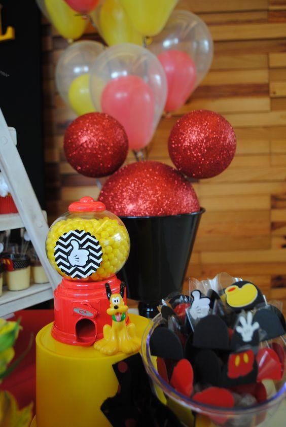 Cabeças de Mickey feitas com bolas de isopor foram um dos destaques da mesa do bolo. repare também nas forminhas personalizadas e no pluto tomando conta das balinhas amarelas dessa festa com tema Mickey idealizada para um menino de dois anos.