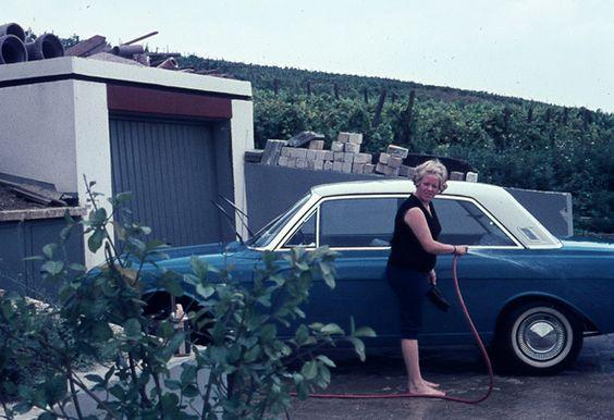 Elke hatte sich gerade erst die Fussnägel lackiert und darf schon wieder den Taunus waschen. Sehr ärgerlich, denn der gerade bezogene Neubau war eines der ersten Häuser in der Strasse und dieselbige bestand 1964 nur aus einem Feldweg. Aber der Wagen musste sauber sein. …  Mehr von Elke und dem grünen Ford mit dem weißen Dach gibt es hier.  Familienarchiv