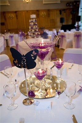 Purple wedding decorating ideas featuring different sized martini glasses filled with water and floating candles.