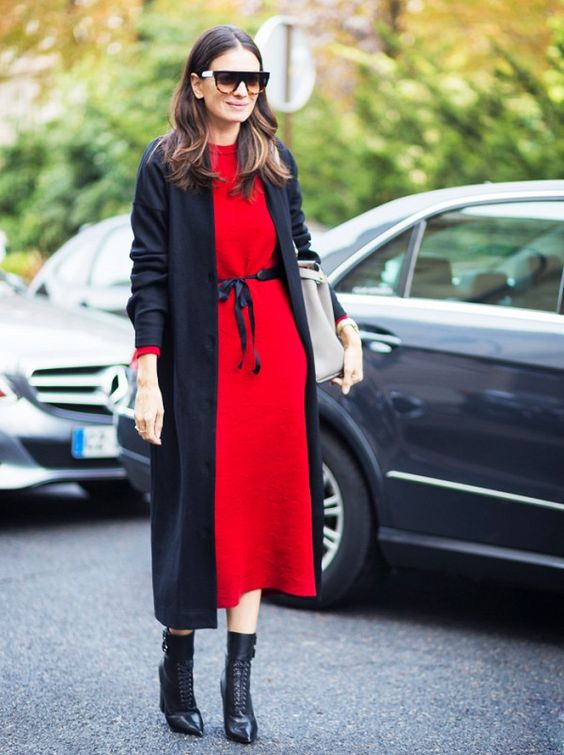 A red midi-dress is belted and paired with a long black coat and black heeled booties.