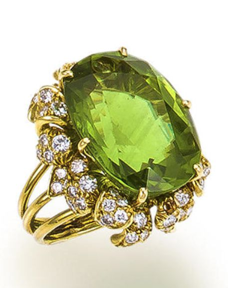 A peridot and diamond ring, Julius Cohen  centering an oval-shaped peridot, weighing 20.52 carats, framed by round brilliant-cut diamond petals; signed Julius Cohen; estimated total diamond weight: 1.20 carats; mounted in eighteen karat gold