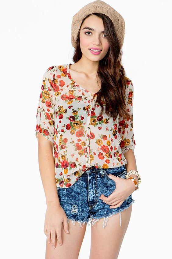 Feel as pretty as a spring day in this blooming floral print blouse. V-neck. Decorative front button closure. Three-quarter inch sleeves with button tabs. Marrow finished hem. Semi-sheer.