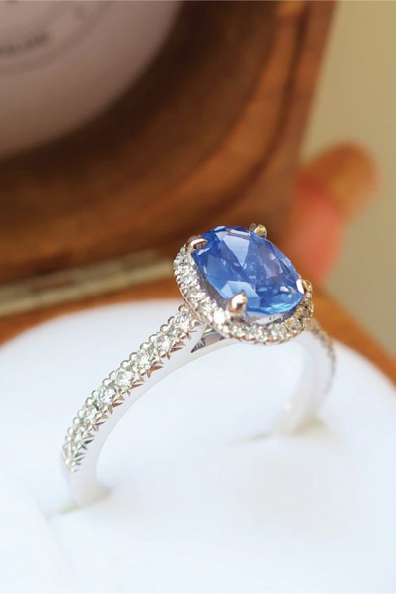 A 1.29ct oval cut blue sapphire claw set in a sleek, diamond studded halo setting. Crafted with 18k white gold metal