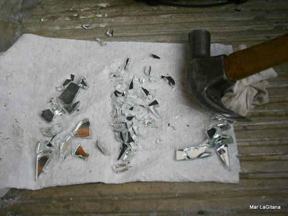 Debemos tener listos nuestros pedazos de espejos triturados, para no cortarnos, envolvemos el pedazo de espejo en una toalla para triturarlo con el martillo, con cuidado de no lastimarnos.