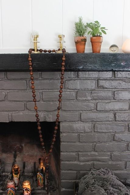 Gray painted brick fireplace with dark mantle.