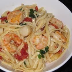 Tender whole scallops and shrimp get a quick saute in hot, garlicky olive oil and butter before taking a brief clam juice simmer. Toss with hot pasta, bright strips of sun dried tomatoes and tangy bits of lemon zest for a refreshing entree or appetizer.