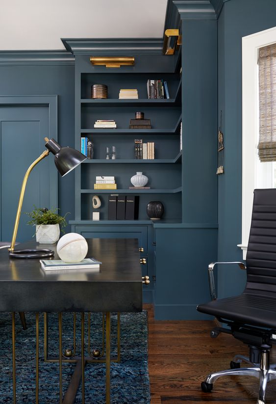 Builtin Bookshelf Lighting creates a soothing evening work environment. #homeoffice #homeofficeideas #homeofficedecor #homeofficelighting #modernofficedecor #modernofficedesign #modernofficeideas #emeraldpaintcolor #builtinbookshelves