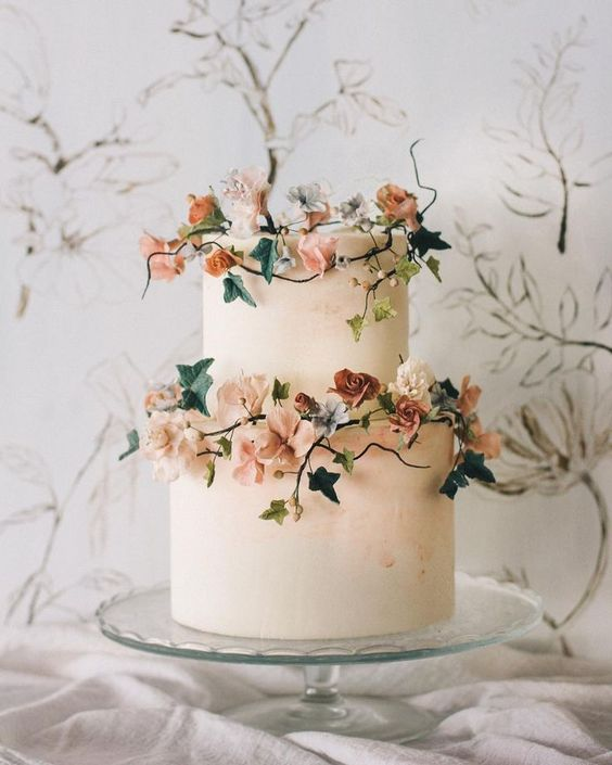 Two tier white wedding cake with autumn inspired foliage for this fall wedding. This beautiful cake on glass stand sitting on this white linen cloth would look beautiful in our stairwell.