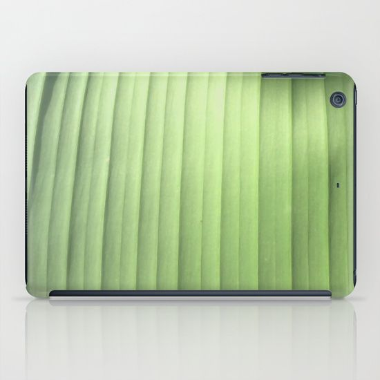 This abstract design is an original photograph of a banana leaf. It was shot at close range, so to speak, focusing on the ribbing of the leaf as it grows out from the center spine. The curving bands of light green shift in color from yellow green in the shadows to a more blueish green in the sunlight.