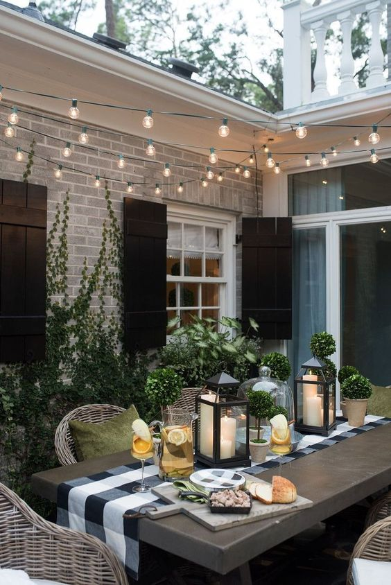 Pretty outdoor table setting with black and white decor and string lights