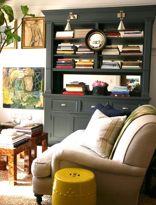 A coat of Farrow & Ball's Down Pipe on the formerly white built-in bookcase added a touch of drama. Gibson also replaced a portrait painting with a circular mirror that helps open up the space, and he introduced a yellow garden stool from Gump's for a jolt of color.