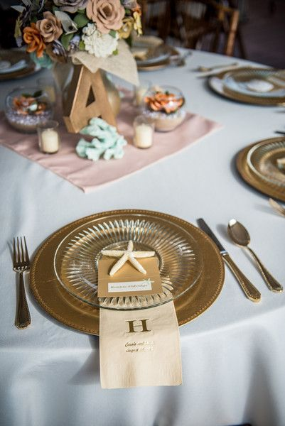 Los ajustes de lugar presentaron cargadores oro, platos de vidrio, servilletas con monogramas hoja de oro, y estrellas de mar.