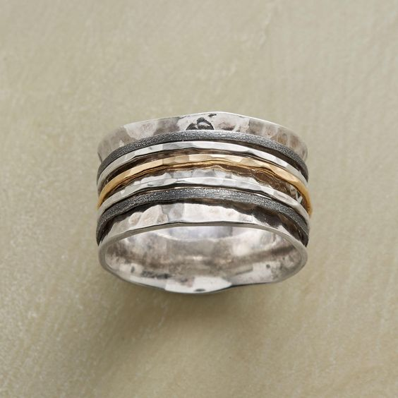 """SPOOLED SPINNER RING--In this mixed-metal spinner ring, five slender rings of sterling silver and 14kt gold spin upon a spooled band of hand-hammered sterling silver. Whole sizes 5 to 9. 1/2""""W."""