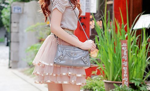 A pink tiered ribbon skirt, white blouse, and gray bag.