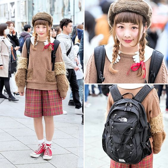 «17-year-old @aki__ki on the street in Harajuku wearing a ushanka hat and cute twin braids hairstyle, a sweater from the Japanese brand Frapbois, plaid…»