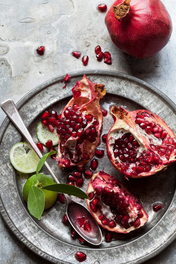 Pomegranate fruit and sliced lime by Nadine Greeff for Stocksy United